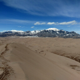 Massive sand dunes with snow capped peaks in the background
