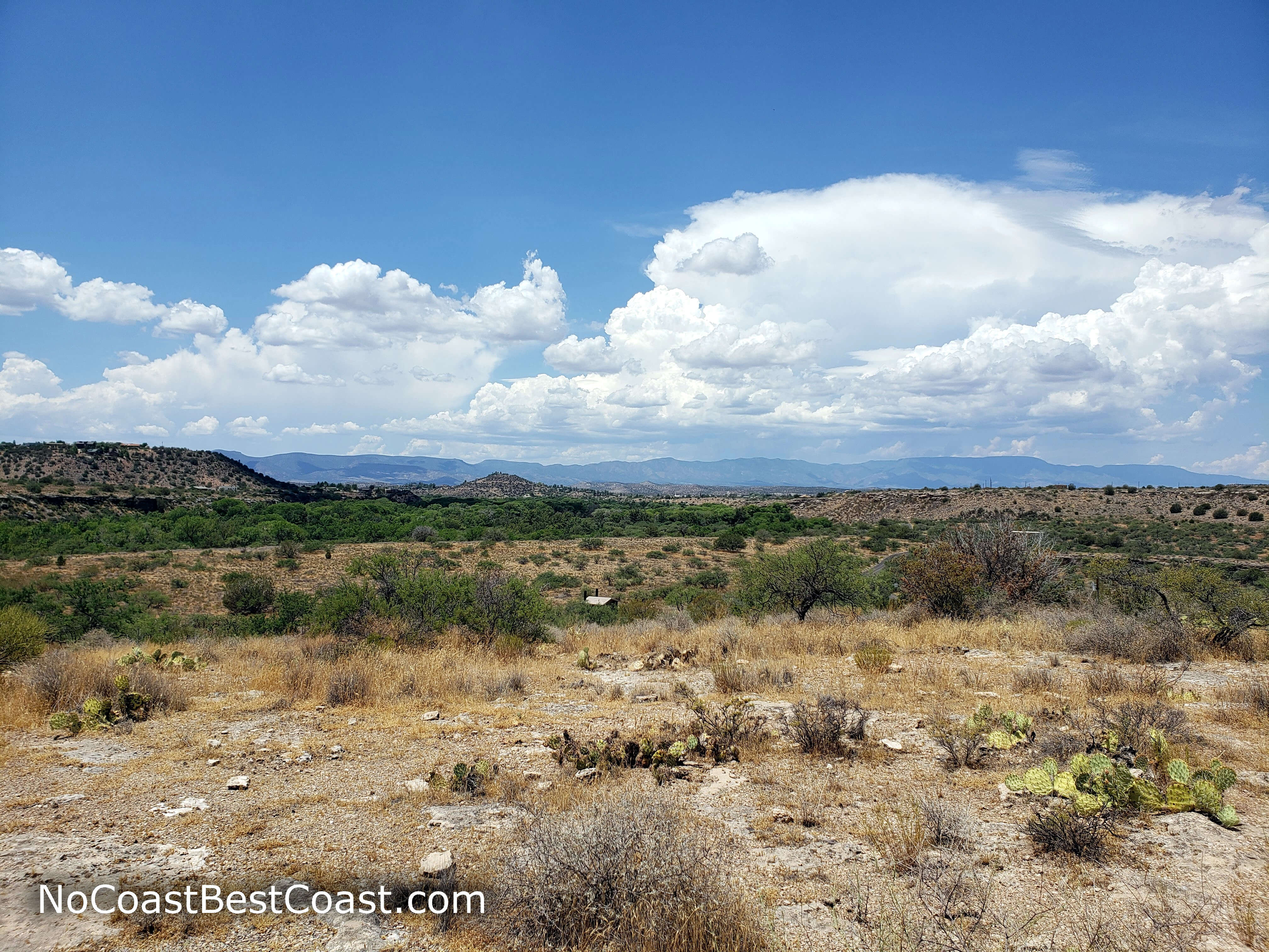 Puffy clouds above the distant desert mountains
