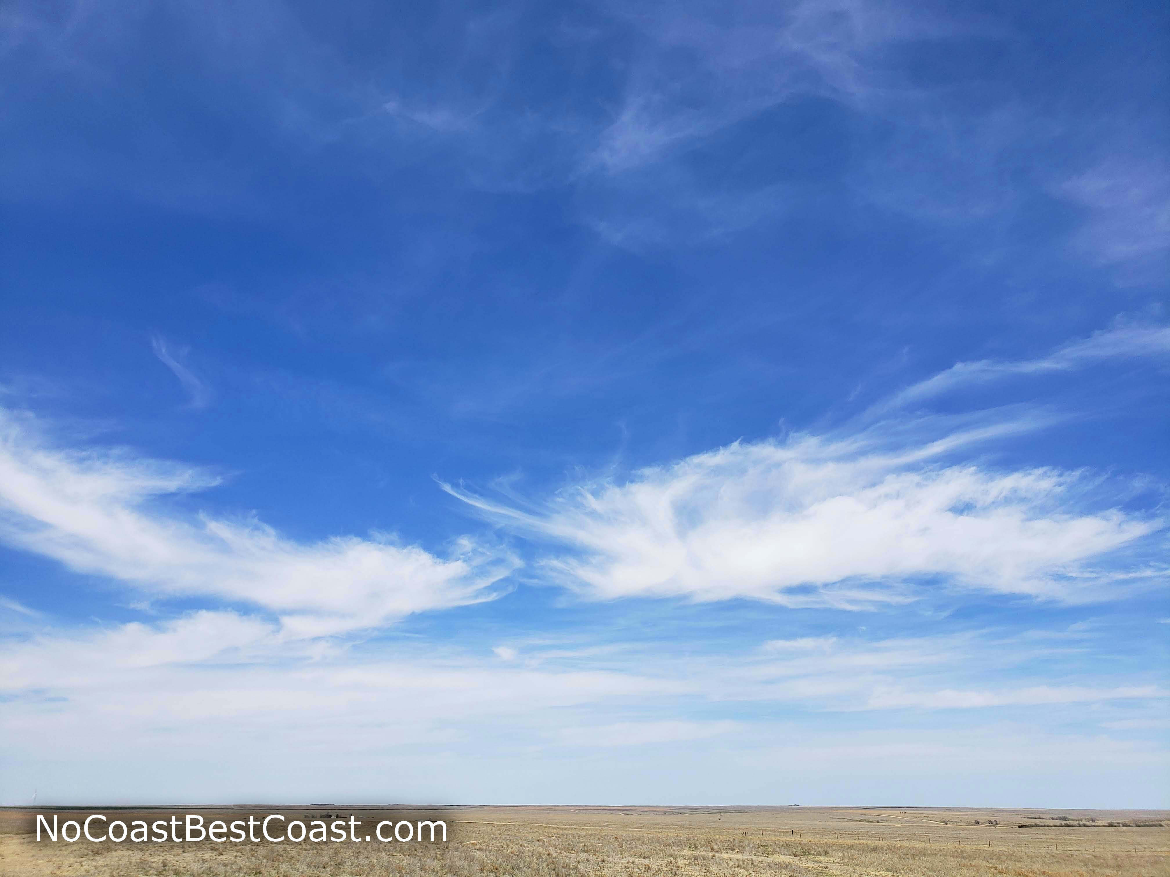 Wispy clouds and endless prairie from the top of Mount Sunflower