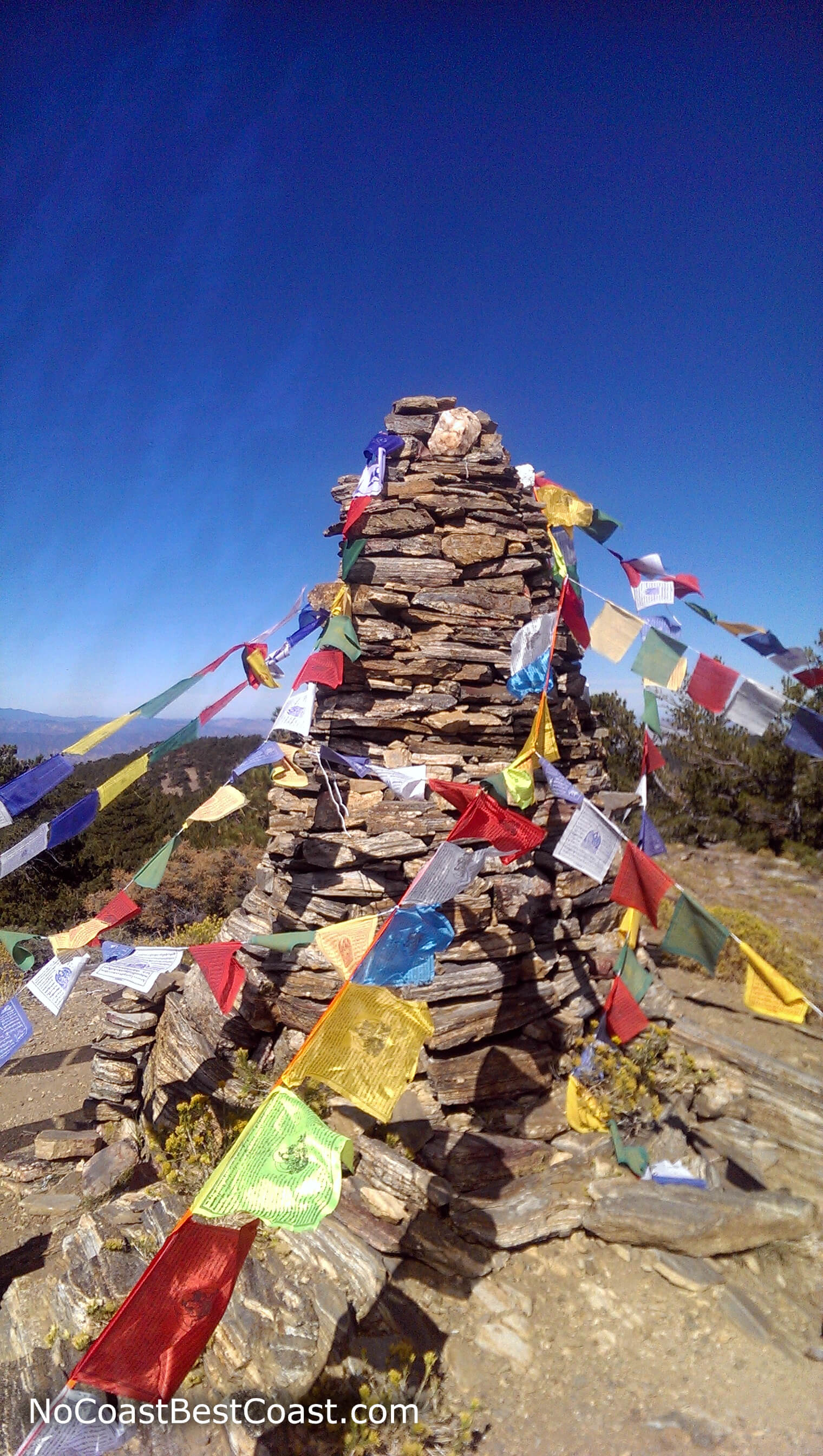 The giant stone cairn adorned with prayer flags marking the summit of Sawmill Mountain